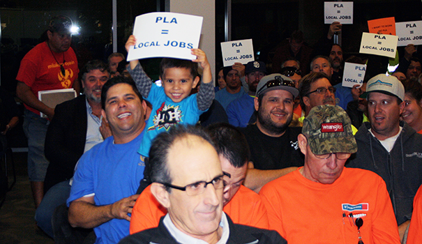 Union workers wearing blue shirts celebrate the Grossmont Cuyamaca Community College District board's decision to adopt a Project Labor Agreement for Proposition V bond projects on Nov. 17 while non-union workers in orange shirts look on. (Photo by Jeff Clemetson)