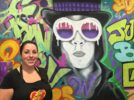 Candy Pros owner Nena Hallak stands in front of the mural of Willy Wonka painted inside her store in Grossmont Center. (Photo by Genevieve A. Suzuki)